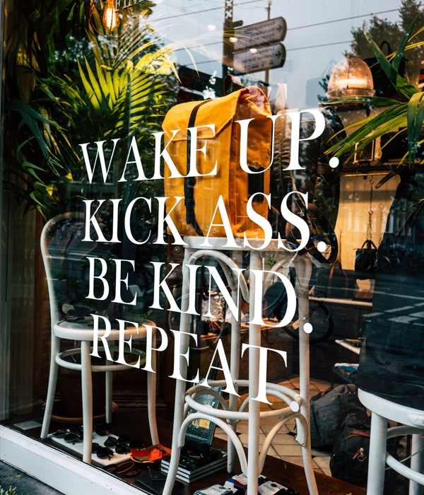 motivational sign on window saying wake up kick ass be kind and repeat